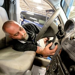 Auto technician Billy Morgan works on installing a new ignition switch during a recall repair on a Chevrolet HHR vehicle at Fitzgerald Auto Mall in Frederick, Maryland.