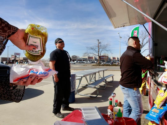 Ronnerick Topahe, left, and Gera Lopez wait in line at Fabulous Frank's of The Four Corners on Thursday next to the Farmington Museum at Gateway Park.