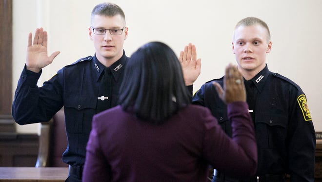 Joseph Cloke, 28, left, and Timothy Murphy II, 21, recite an oath as the pair were sworn into the Elmira Police Department as officers Friday at City Hall.
