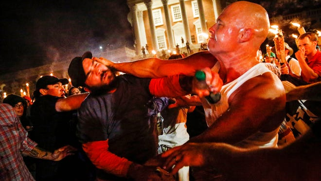 A white nationalist, right, fights with a counterprotester on the University of Virginia campus in Charlottesville, Va., on Friday, Aug. 11, 2017. Before the clash the white nationalists marched with torches through the campus.