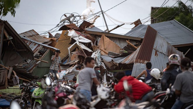 Residents look for their belongings amid the debris of destroyed houses in Palu in central Sulawesi, Indonesia, on Sept. 29, 2018, after a strong earthquake and tsunami struck the area.