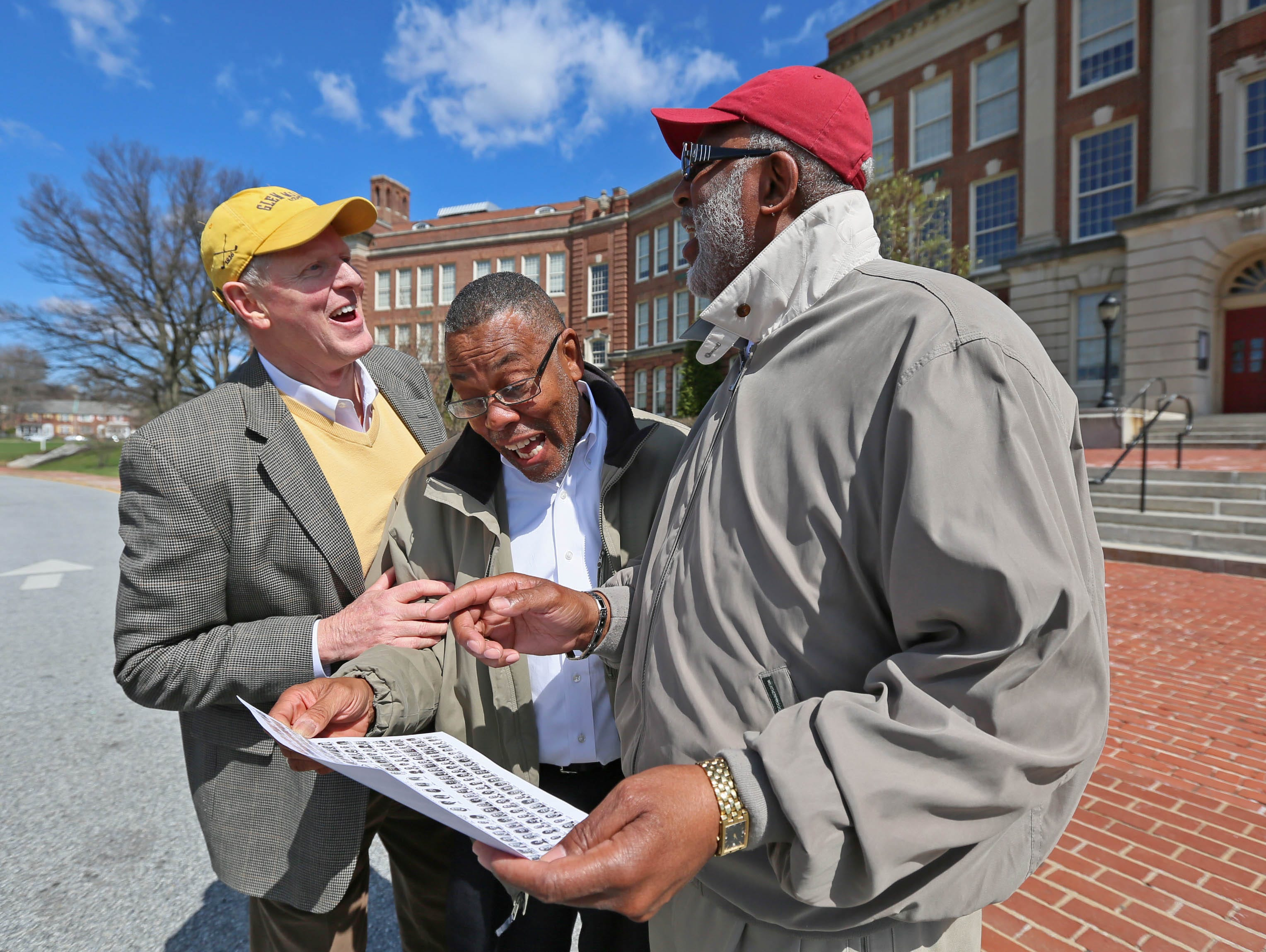 Former 1968 state championship basketball teammates Randy Johnson, Clinton Tymes, and Ron Smith share laughs while looking at their old class photographs in front of the former P.S. du Pont High School.
