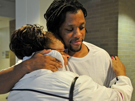 Kenneth Kagonyera hugs his grandmother Alice McLean after being proclaimed innocent and released from prison after being jailed for 11 years on murder charges in 2011.
