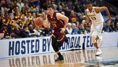Loyola-Chicago guard Clayton Custer dribbles on a fast