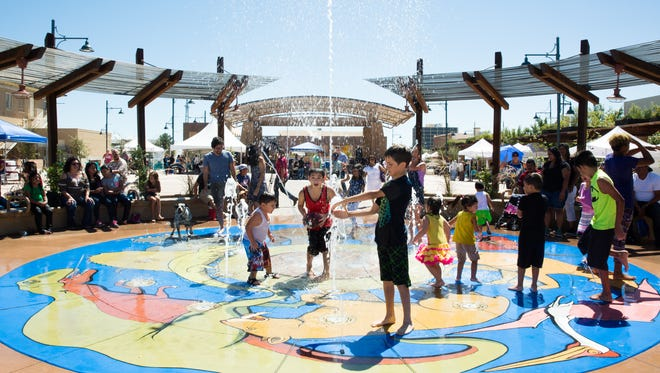Ten-year-old Gabriel Soltero, center, hold a ball while playing in the splash pad with other kids on Saturday, September 17, 2016, during the grand opening of the downtown Plaza de Las Cruces.