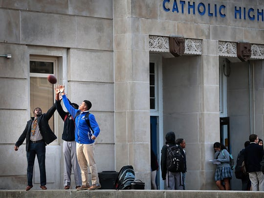 Kids wait for a ride home after school at the Catholic