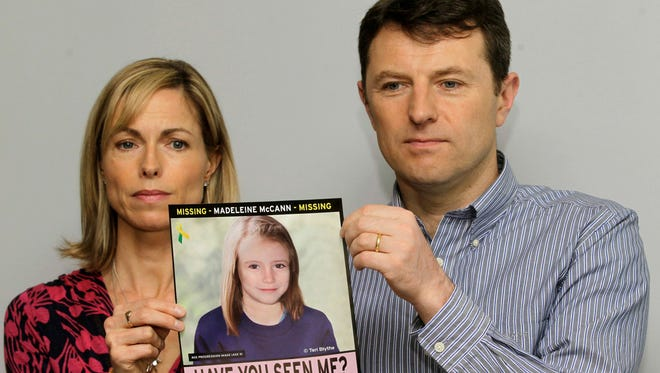 In this May 2, 2012, file photo, Kate and Gerry McCann pose for the media with a missing poster depicting an age progression computer generated image of their daughter Madeleine at nine years of age.