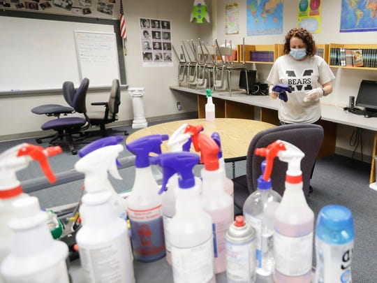 Charo Woodcock cleans a classroom at McClelland Elementary School on June 22 in Indianapolis.