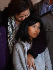 Mariyana Sunarto, wife of Harry Pangemanan hugs their 11-year-old daughter during a news conference at Cai's Cafe in Metuchen, celebrating a federal district court judge granting a temporary restraining order halting deportations of Indonesian Christian residents of Central Jersey in response to a federal class action lawsuit.