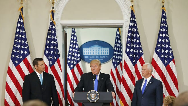 President Donald Trump, with Kansas Secretary of State Kris Kobach, left, and Vice President Mike Pence,  speaks at a meeting of the Presidential Advisory Commission on Election Integrity on Wednesday in the Eisenhower Executive Office Building at  the White House complex in Washington.