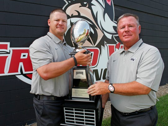 Joe Woodley, left, and his father, Mike Woodley, holding the NAIA championship trophy in 2015.