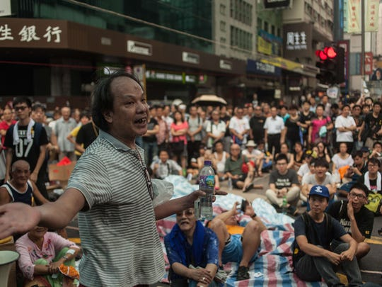 A man supporting the government speaks to a crowd of pro-democracy activists in the Kowloon district of Hong Kong on Tuesday, Sept. 30, 2014. Hong Kong has been plunged into the worst political crisis since 1997 as pro-democracy activists took to the streets to demand full voting and election rights.