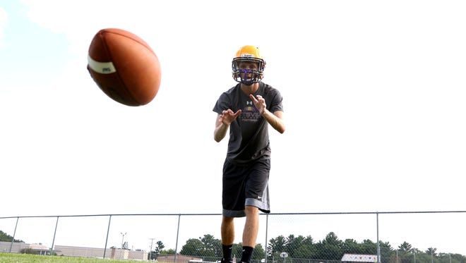 A Pittsville High football player catches a low pass during football practice at Pittsville, August 2, 2016.