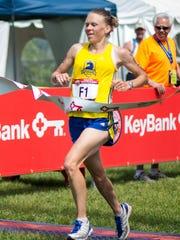 Huntington resident Kasie Enman runs across the finish