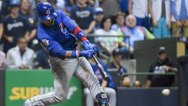 The Cubs' Javier Baez drives in the tying run with an RBI single in the ninth inning against the Brewers at Miller Park in Milwaukee.
