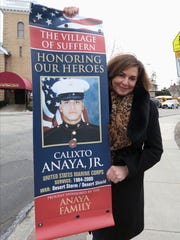 Amanda Arroyo holding a banner, honoring her husband, Calixto Anaya Jr., which will be placed on a street light pole in Suffern March 24, 2017.