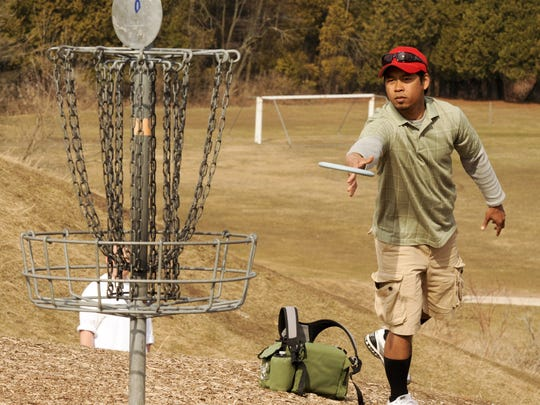 Jimi Dao of Manitowoc plays in the first round of the Skyline Amateur Series disc golf tournament at Silver Creek Park in Manitowoc in 2012.