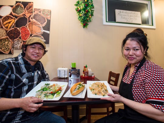Cousins Man Gurung, left, and Deoki Gurung with offerings of, from left,  wide noodles with vegetables, a banh mi Vietnamese pork sandwich, and peanut street noodles at Namuna Asian Kitchen in Winooski on Tuesday, December 5, 2017.