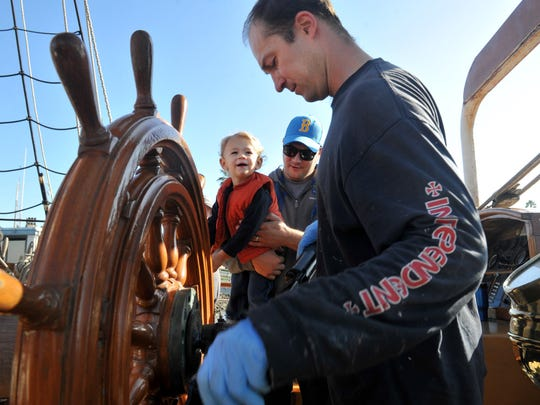 William Stuteville (center), 22 months, held by his father Jeff, watch as assistant engineer Johann Steinke does maintenance work at the helm aboard the tall ship Hawaiian Chieftain during a dockside tour of it and the tall ship Lady Washington in 2014.