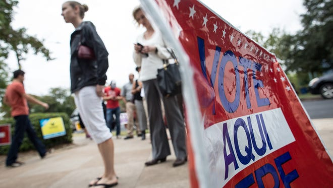 Voters wait in line to cast ballots in Austin last November. Civil and voting rights groups have challenged recent actions by the Texas secretary of state's office questioning thousands of registered voters who officials allege are non-U.S. citizens.