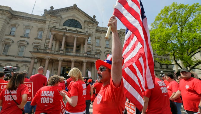 Gino Gianfrancesco of Matawan, a facility technician for Verizon, holds an American flag as Verizon workers and unions striking hold a rally in front of the State House in Trenton, NJ Monday, April 25, 2016.