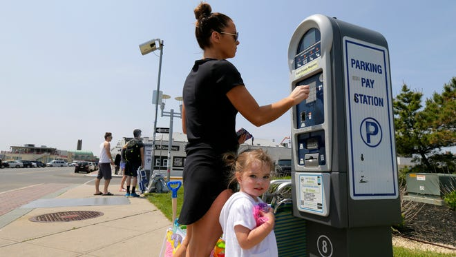 Meghan Boyle of Colts Neck pays for parking with her 2-year-old daughter, Annabelle D'Agostino, at a parking pay station on Ocean Avenue in Asbury Park, NJ Wednesday May 25, 2016.