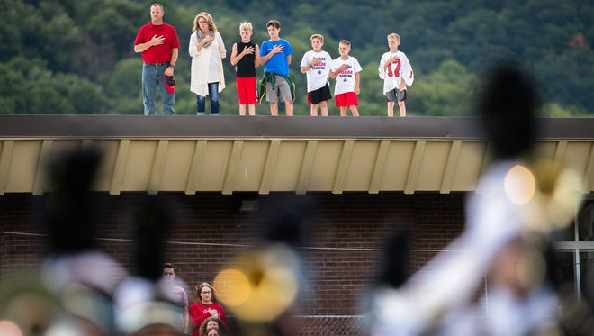Fans stand for the national anthem before Pisgah's rival football game against Tuscola Friday, September 1, 2017.