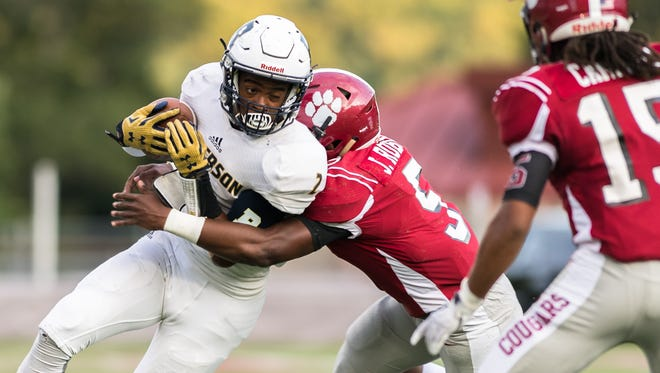 Roberson's Kobe Miles is tackled by Asheville's Jordan Robinson during their game Friday, September 8, 2017.