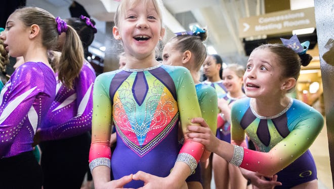 "Payton McNally, 10, of Premier Athletics based in Knoxville, Tennessee, grabs the arm of teammate Lily Hughes, 9, asking her, ""are you scared?"" before their team is announced and escorted onto the floor before competition begins at the Gymnastics Gala invitational at the U.S Cellular Center in Asheville, Saturday, January 6, 2017. Teams came from Florida, Georgia, North Carolina, South Carolina, and Tennessee."