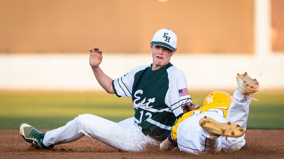 East Henderson's Connor Wilmot tags out North Henderson's Hunter Stackhouse as he dives into second base at McCormick Field in Asheville Tuesday, April 3, 2018. North Henderson won 7-4 in seven innings.
