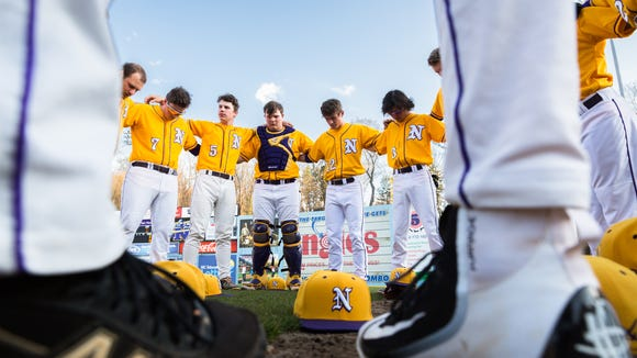 The North Henderson baseball team joins in a prayer before their game against East Henderson at McCormick Field in Asheville Tuesday, April 3, 2018. North Henderson won 7-4 in seven innings.