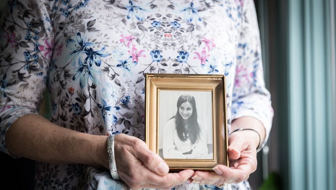 Jean Parks, a psychologist and a board member of the support group, Murder Victims' Families for Reconciliation, in her home in Fletcher, holding a photo of her sister Betsy Rosenberg who was beaten to death in 1975 near the North Carolina State University in Raleigh at the age of 24.