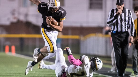 Tuscola's Brandon Cullins runs the ball knocking over Roberson's Kobe Miles during their game Friday, October 27, 2017.