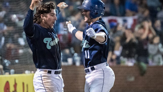 The Asheville Tourists' Ryan Vilade celebrates with Casey Golden after his home run during the Tourists' season opener against the Columbia Fireflies Thursday, April 12, 2018.