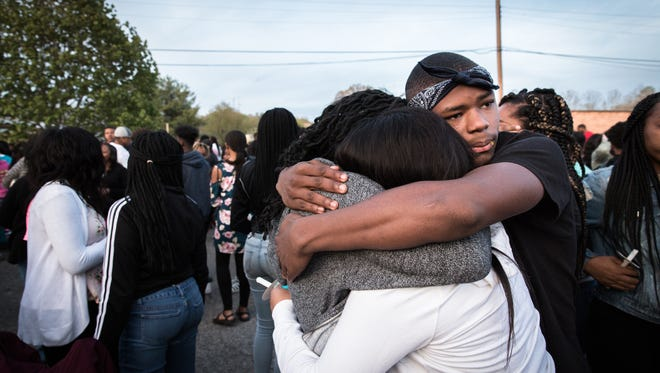 Zavian Smith Casey, Kaila Barrow, and Te'Asya Marshall Timpson embrace following a vigil at New Mount Olive Church Saturday, April 21, 2018, for Erica Smith, 32, Harmony Smith, 13, and Keith Whitmire, 15, who were all shot and killed on Wednesday by Smith's boyfriend Maurice Garner.