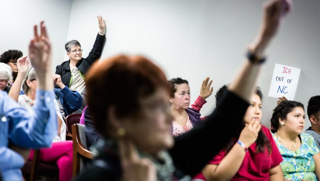 Attendees of a 287 (G) Steering Committee meeting raise their hands to address U.S Immigration and Customs Enforcement officials about the program in Henderson County, Wednesday, April 25, 2018.
