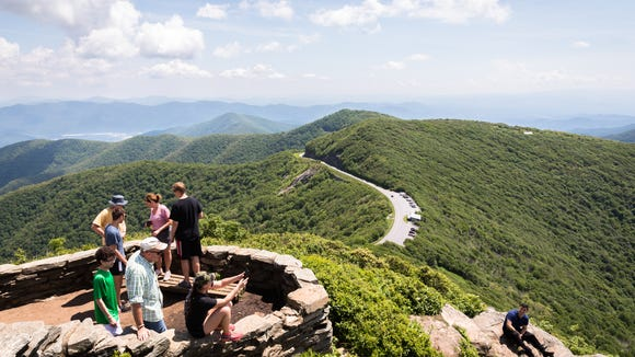Hikers take in the view at the summit of the Craggy Pinnacle trail, Friday, June 15, 2018.