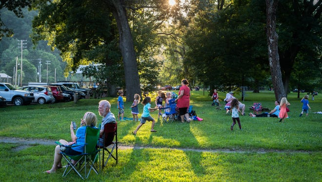 Families sit on Blannahassett Island in Marshall waiting for the fireworks display Wednesday, July 4, 2018.