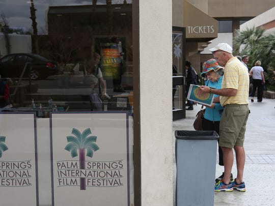 People look at the showtimes for the Palm Springs International Film Festival at the Regal Cinemas in Palm Springs, January 8, 2018. l