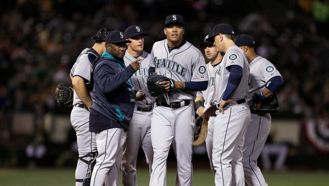 Seattle Mariners' Taijuan Walker, center, is removed by manager Lloyd McClendon, front left, in the fourth inning of a baseball game against the Oakland Athletics on Friday, April 10, 2015, in Oakland, Calif.