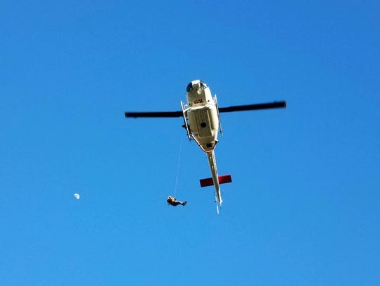 A Cal Fire firefighter is lowered from a helicopter