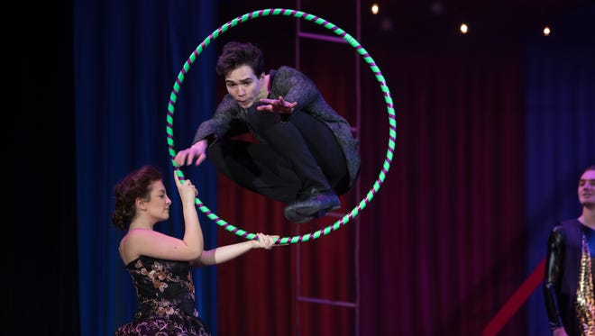 """Noah Grimm jumps through a hoop as part of his role as lead actor in the Brighton High School winter musical """"Pippin."""""""