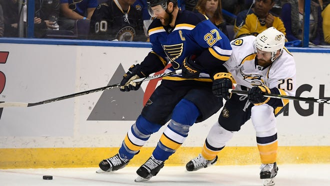 St. Louis Blues defenseman Alex Pietrangelo (27) and Nashville Predators right wing Harry Zolnierczyk (26) battle for the puck during the first period of game 5 in the second round NHL Stanley Cup Playoffs at the Scottrade Center Friday, May 5, 2017, in St. Louis, Mo.
