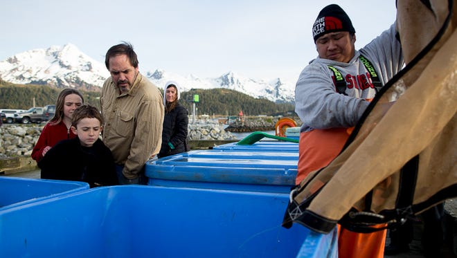 Locals watch as workers unload fish into crates on a public dock in Cordova, Alaska.
