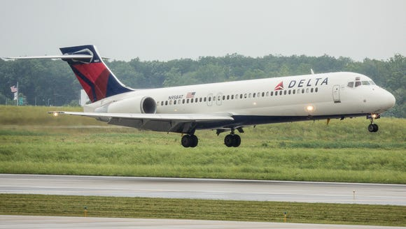 A Delta Boeing 717 lands at a rainy Detroit Metropolitan