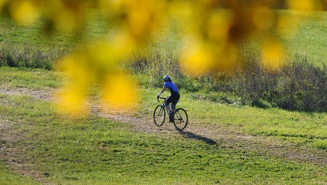 A bicyclist rides up the sledding hill along Lawrence Creek at Fort Harrison State Park.
