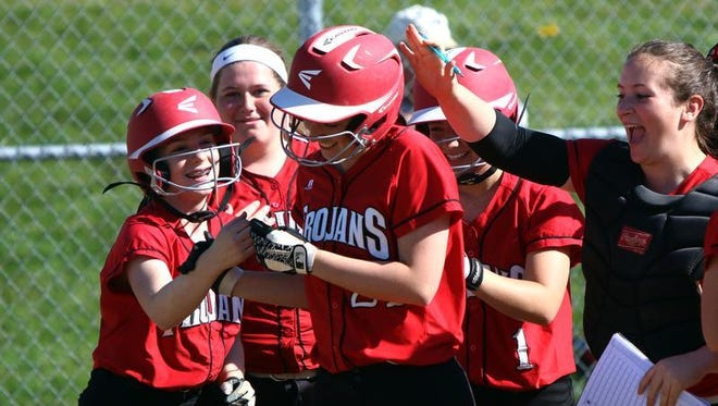 Bishop Ahr's Colleen Scharlow gets congratulated by teammates after hitting a two-run home run against Monroe on Wednesday.