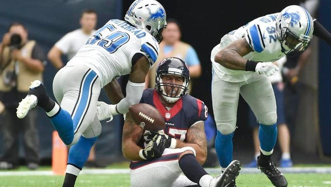 Lions middle linebacker Tahir Whitehead, left, breaks up a pass intended for Texans tight end C.J. Fiedorowicz during the first half on Sunday in Houston.