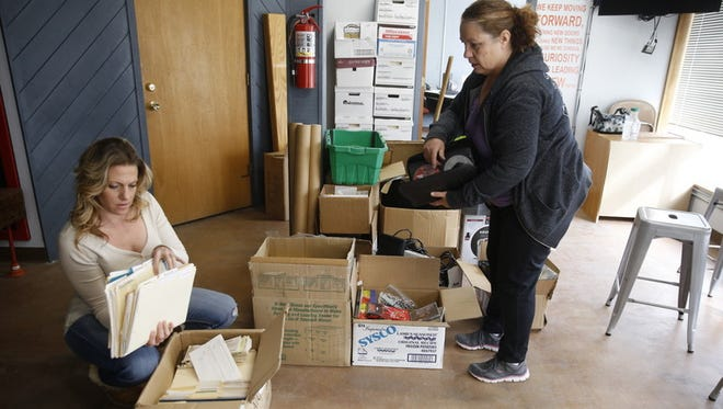 President Theresa Bailey, left, and Treasurer Annette Davis of the Aztec Chamber of Commerce unpack boxes Saturday outside their new office in the city's business incubator, located at 119 S. Church Ave.