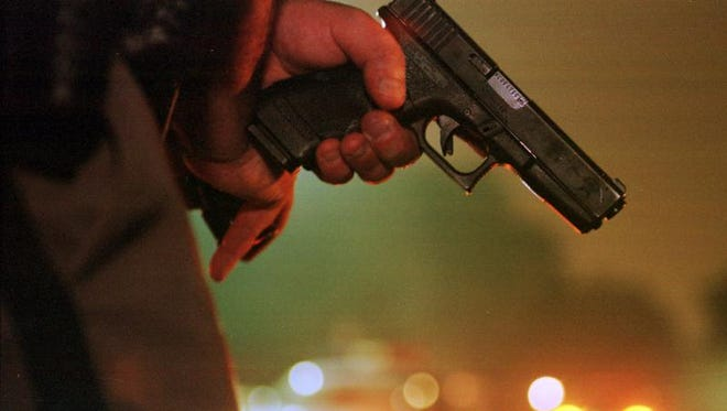 A law enforcement officer holds a 9mm Glock pistol at the ready during a burglary call.